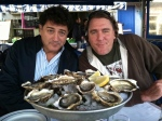 Two guys and a pile of oysters.